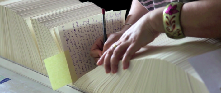 Une femme écrivant dans le livre d'or exposé au Musée de l'Elysée en septembre 2013