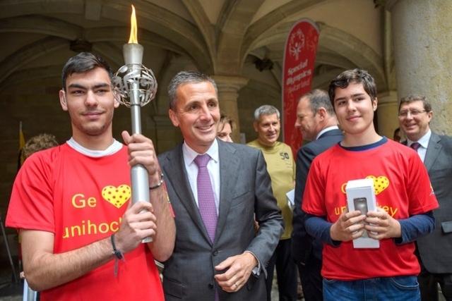 ©24heures - Le président du Conseil d'État Francois Longchamp aux côtés de deux athlètes.
